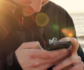 Person bedient iPhone vor Meer-Kulisse